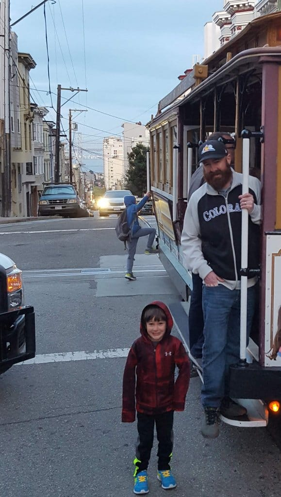 Eli and Chad standing next to the cable car on the way to Ghirardellil Square in San Francisco
