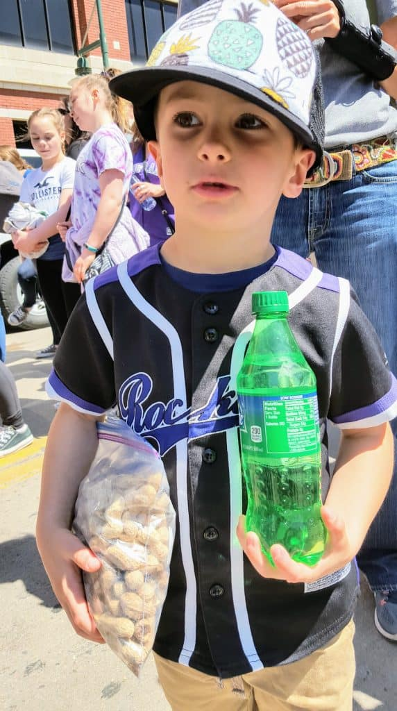 Eli standing outside coors field with a sprite and peanuts