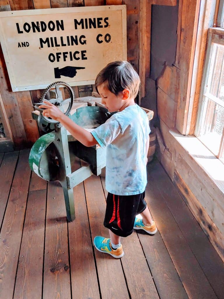 Eli looking at an old washing machine at South Park City in Colorado
