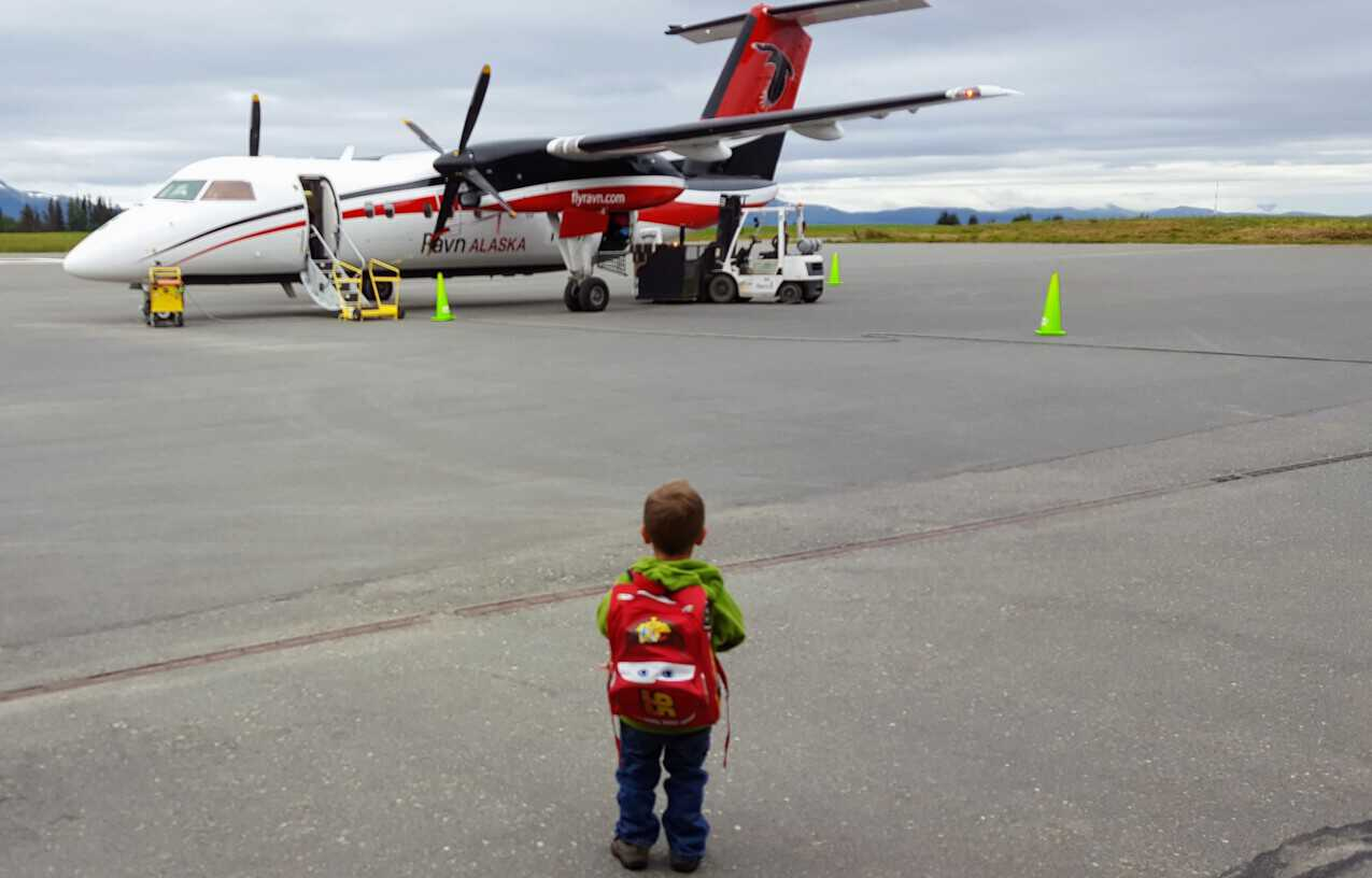 Eli standing in front of a twin prop airplane on the runway