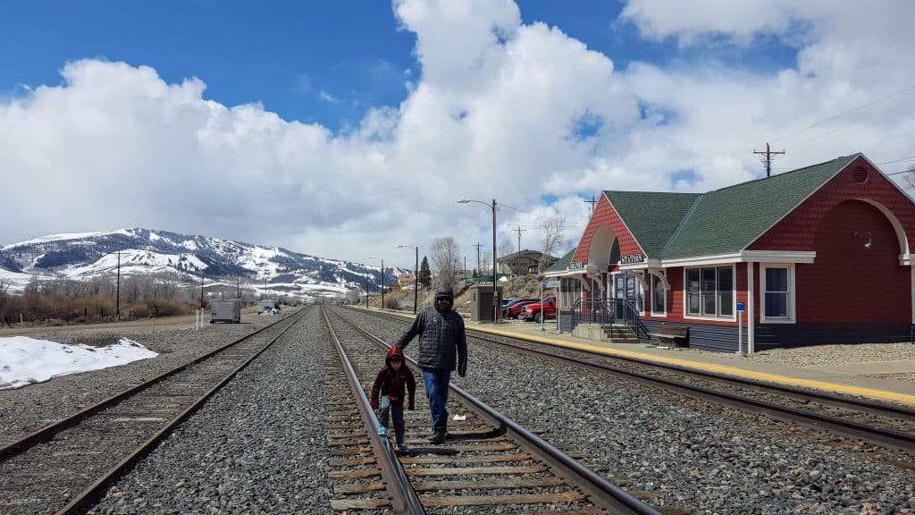 father and son on the train tracks in Colorado with snow covered mountains