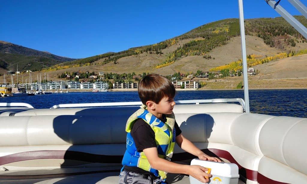 boy on a pontoon boat on lake dillon in the fall