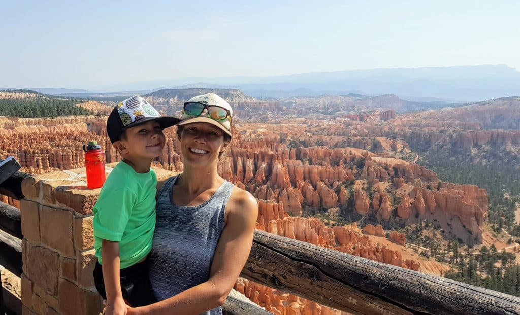 Mom holding her son with a view of Bryce Canyon National Park in the background