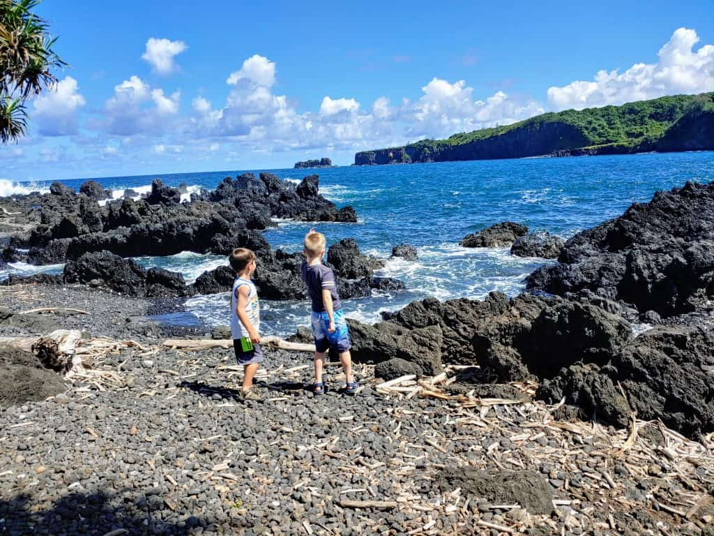 two boys throwing rocks into the ocean on the Keanae peninsula Maui