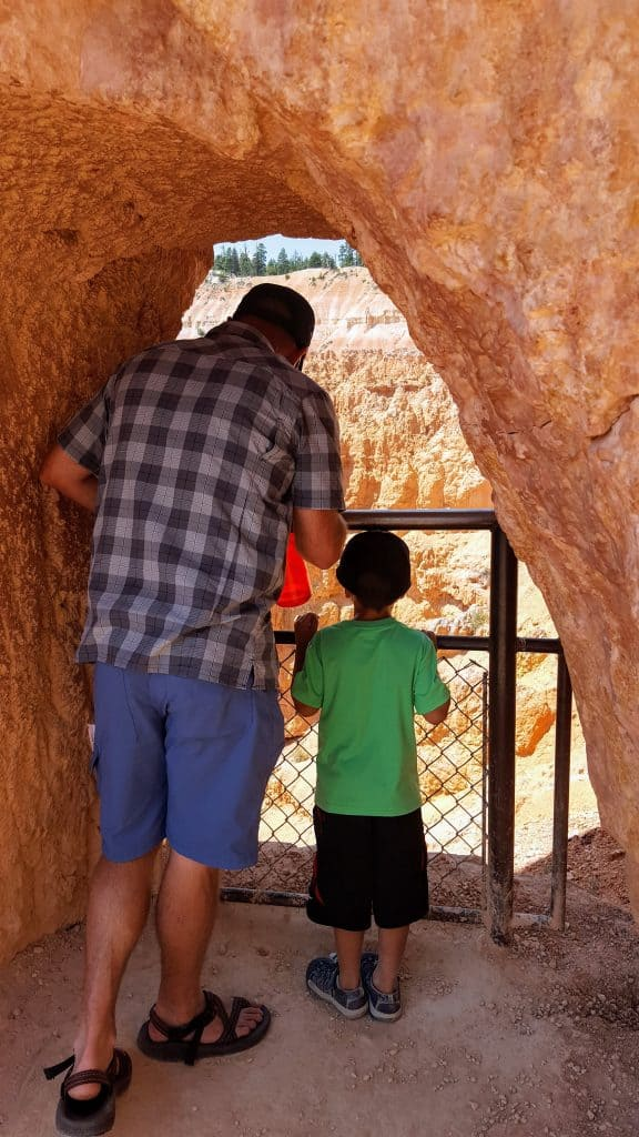 Father and son looking through a rock arch over Bryce Canyon National park