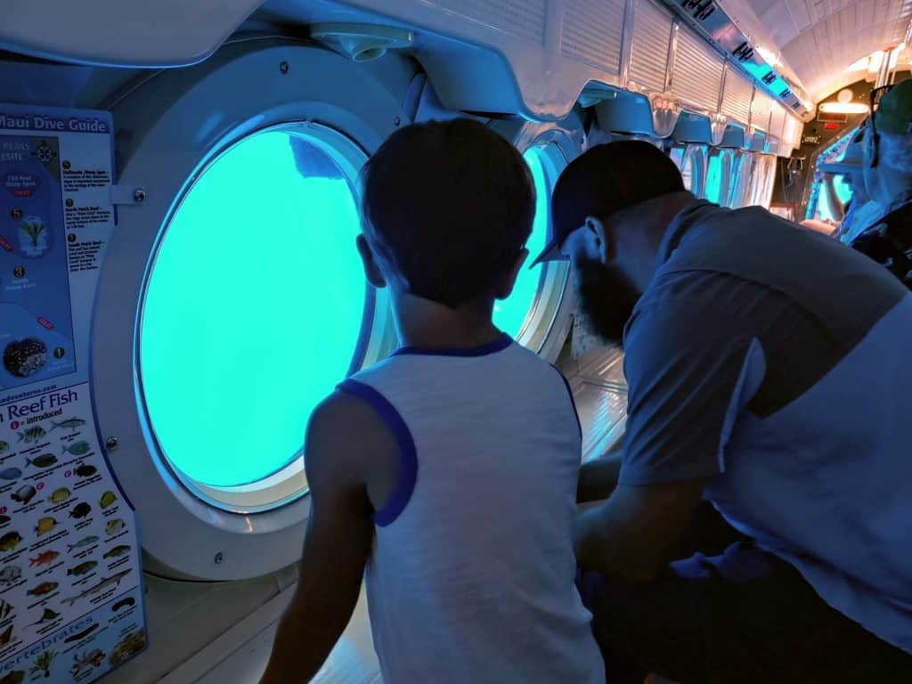 father and son looking out the window in the atlantis submarine tour