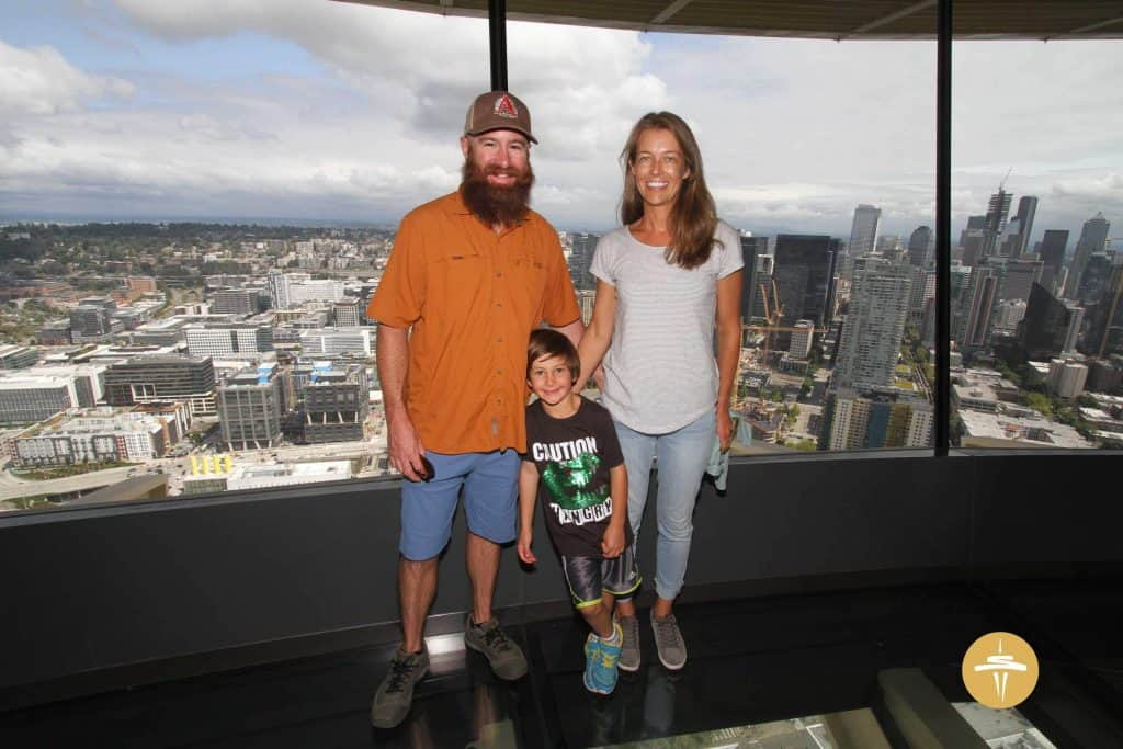 Family in the space needle with Seattle in the background
