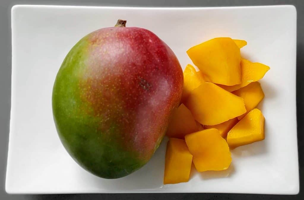 One whole mango and a mango sliced up on a white plate - Fruit in Hawaii