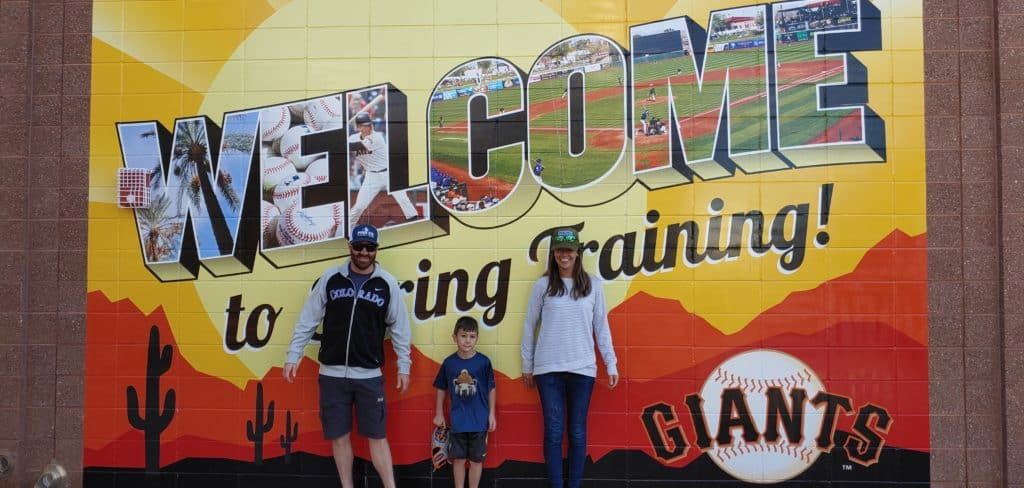 Parents and a child standing in front of a Giants Spring Training Sign painted on a brick wall