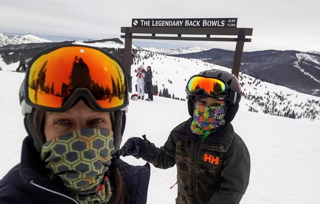 Mom and son standing in front of the back bowl sign at Vail Ski Resort