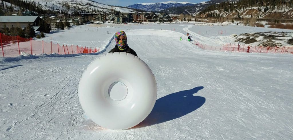 boy standing on top of the Runway sledding hill in Breckenridge