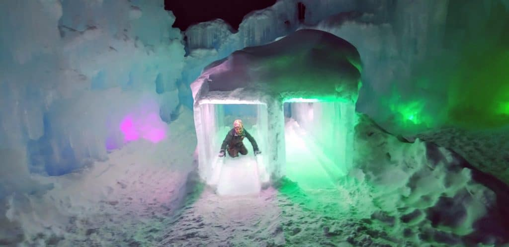 Child sliding down an ice slide at the Dillon Ice Castles