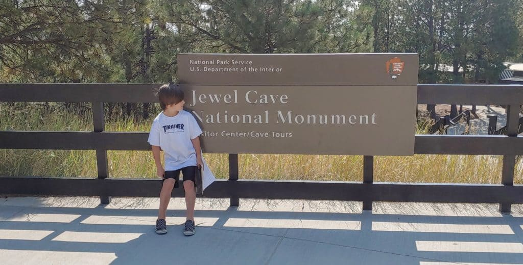 boy standing in front of the Jewel Cave National Monument sign in the black hills of south dakota