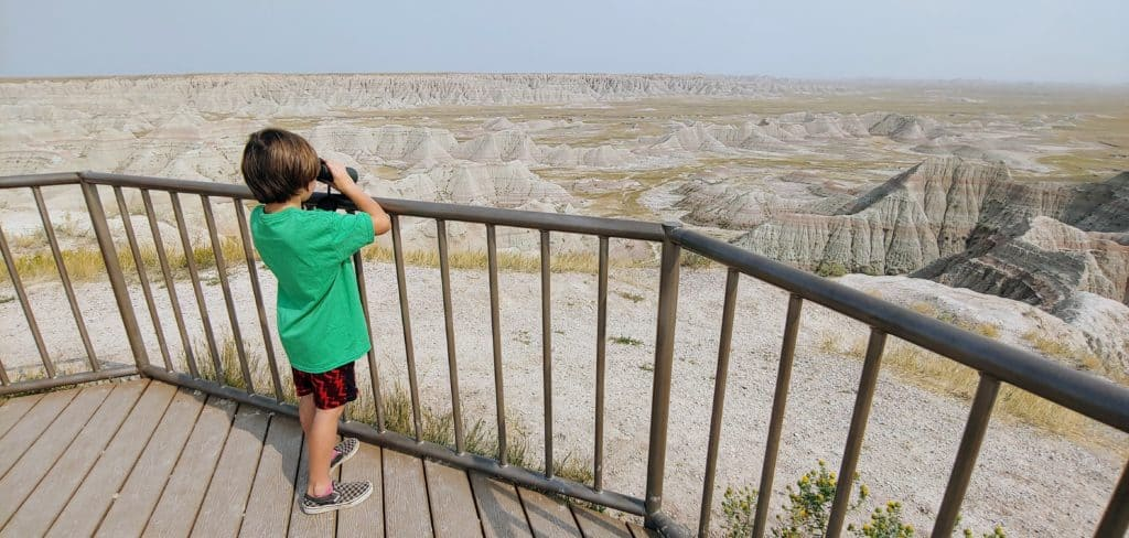 Young boy looking through binoculars at a viewpoint in Badlands National Park