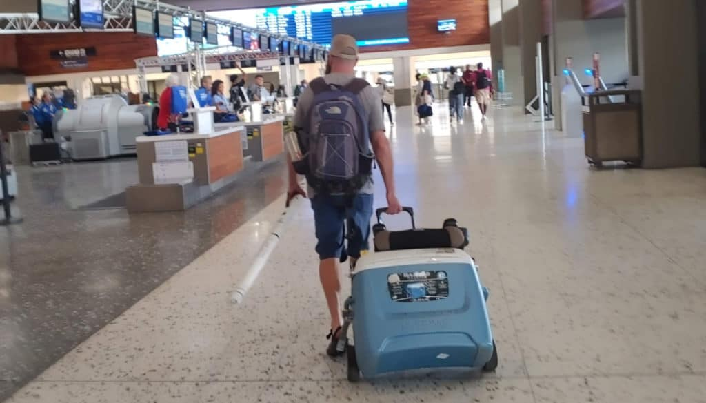 Man walking through the airport pulling a cooler on wheels as his checked luggage
