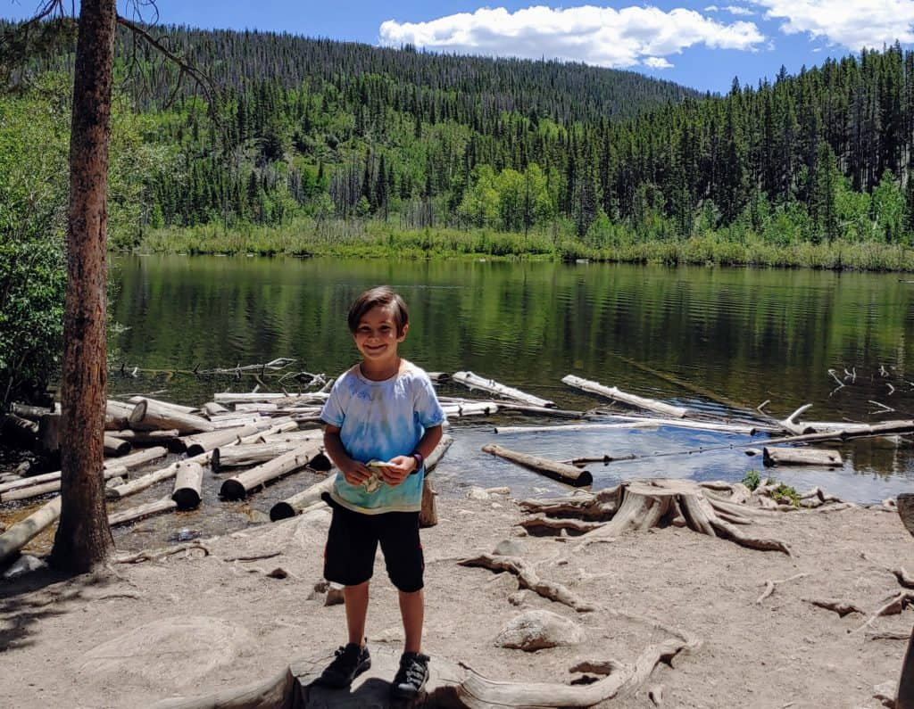 Boy standing in front of Rainbow Lake in Frisco, Colorado