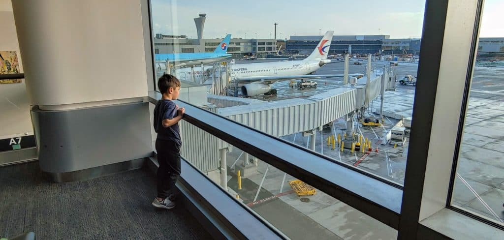 Child looking out the window at an airplane at the airport