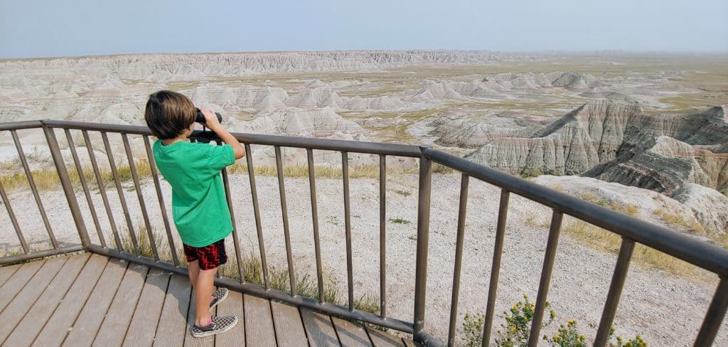 boy looking through binoculars at a viewpoint in Badlands National Park