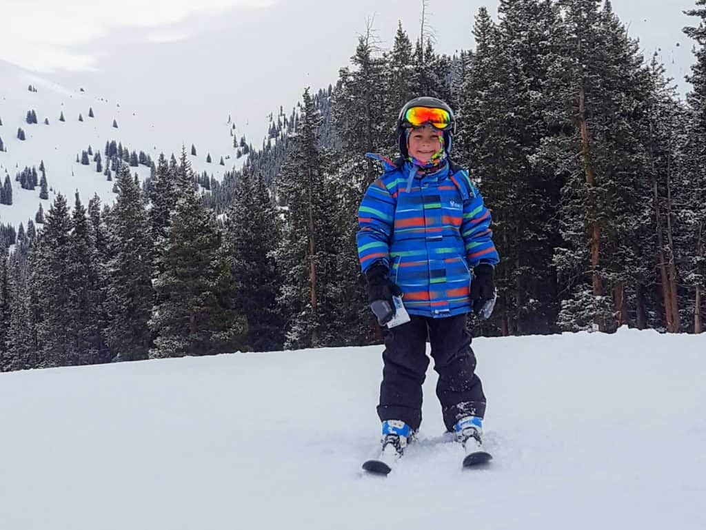 boy standing on skis at a ski resort in Colorado