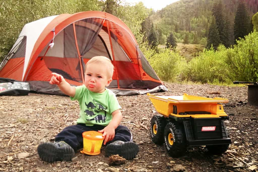 baby sitting in the dirt in front of a tent eating snacks