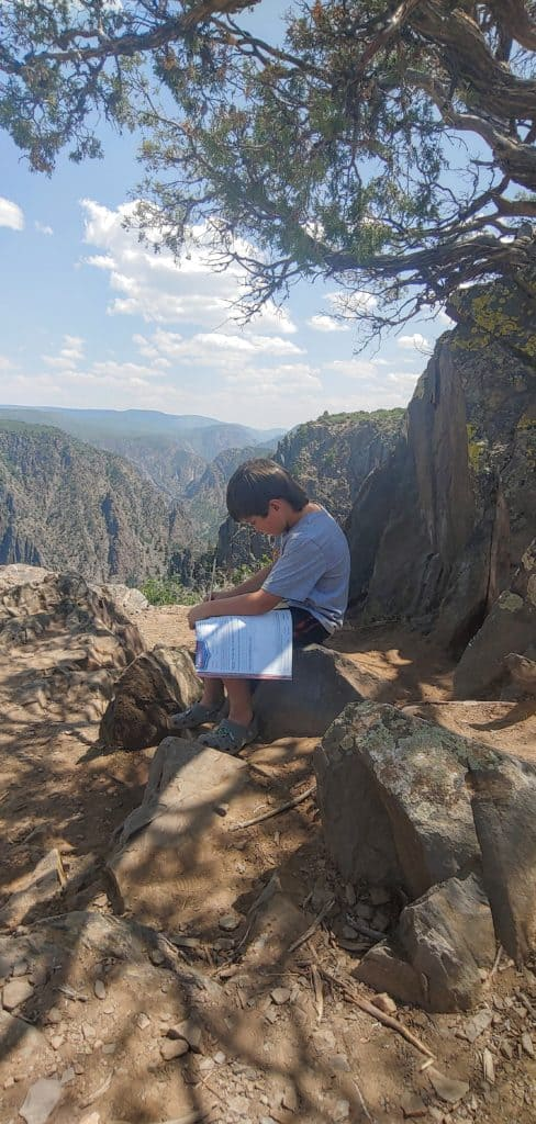 boy working in his Junior Ranger book under a tree at Black Canyon of the Gunnison National Park in Colorado
