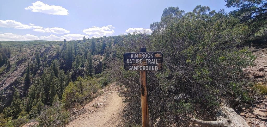 hiking trail sign and hiking trail at Black Canyon of the Gunnison National Park in Colorado